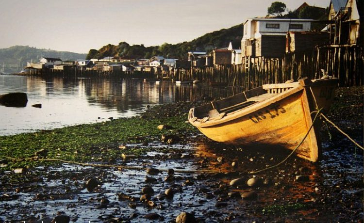fishing boat at sunrise near the palafitos, castro, chile